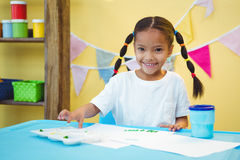 Smiling girl who is finger painting Royalty Free Stock Photos