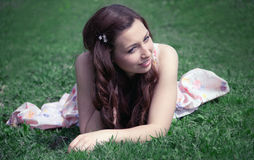 Smiling girl who is sitting on the grass Stock Photo