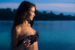 Smiling girl with wineglass. Young lady on sea background. Celebrating birthday at sea resort. Youth and beauty Royalty Free Stock Images