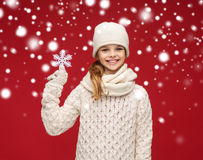 Smiling girl in winter clothes with big snowflake Stock Image