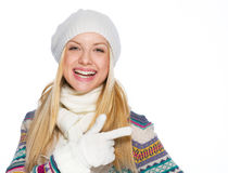 Smiling girl in winter clothes pointing on copy space Stock Photo