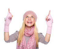 Smiling girl in winter clothes pointing up on copy space Royalty Free Stock Photo