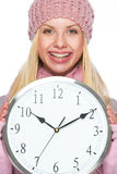 Smiling girl in winter clothes showing clock Stock Photos