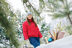 Smiling girl in winter forest near basket Royalty Free Stock Photos
