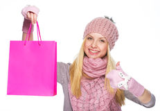 Smiling girl in winter hat showing shopping bag and thumbs up Royalty Free Stock Photography
