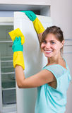 Smiling girl wiping fridge Royalty Free Stock Photography