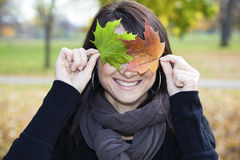 Smiling Girl With Colorful Leaves Stock Images