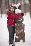 Smiling girl with woody hare. Smiling girl embracing woody hare in a winter park Royalty Free Stock Photography