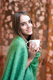 Smiling girl in a woolen blanket drinking coffee Stock Photos