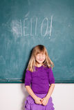 Smiling girl with word hello on chalkboard Stock Images
