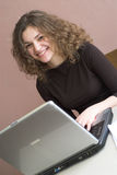 Smiling girl is working with laptop. Focus on face royalty free stock image