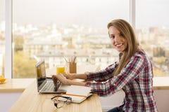 Smiling girl working on laptop Royalty Free Stock Image