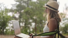 Smiling girl working on laptop outdoors in summer vacation.