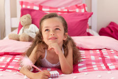 Smiling girl writing on bed Stock Images