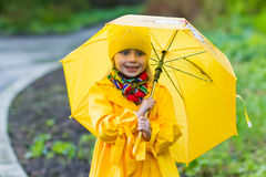 Smiling girl in a yellow dress with an umbrella on a rainy spring sunny day Stock Photo