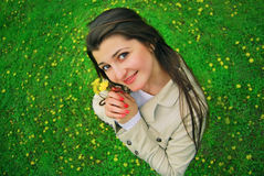 A smiling girl with yellow flowers. And a green  field with yellow flowers Stock Image