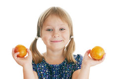 Smiling girl with yellow plums. Happy smiling girl looking at a camera holding in her hands two yellow plums stock photography