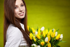 Smiling girl with yellow tulips. Royalty Free Stock Image