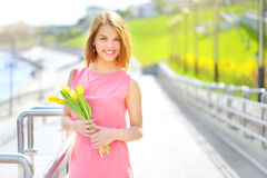 Smiling girl with yellow tulips Stock Photography