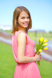 Smiling girl with yellow tulips Stock Photos