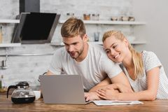 Smiling girlfriend hugging boyfriend in kitchen and he. Using laptop stock photography