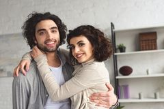 Smiling girlfriend hugging boyfriend and they looking at camera. At home stock photos