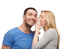 Smiling girlfriend telling boyfriend secret. Relationships, love and couple concept - smiling girlfriend telling boyfriend secret Stock Photography