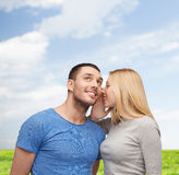 Smiling girlfriend telling boyfriend secret Royalty Free Stock Photos