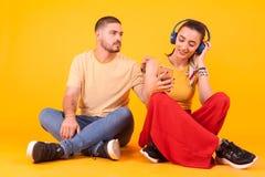 Free Smiling Girlfriend With Headphone Ignoring Her Boyfriend Royalty Free Stock Photo - 160732575