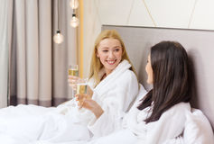 Smiling girlfriends with champagne glasses in bed Royalty Free Stock Photo