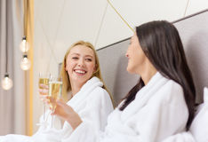 Smiling girlfriends with champagne glasses in bed Stock Photography