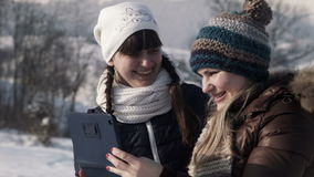 Smiling girlfriends do selfie on the mountain. Two smiling girlfriends do selfie on the mountain in the winter using digital tablet stock footage