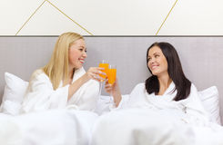 Smiling girlfriends having breakfast in bed Royalty Free Stock Photo