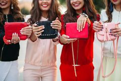 Smiling girlfriends with manicure holding handbags.