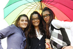 Smiling girlfriends under umbrella Royalty Free Stock Images