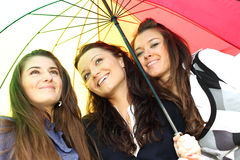 Smiling girlfriends under umbrella Royalty Free Stock Photography
