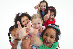 Smiling girls all looking upwards with thumbs up Royalty Free Stock Photos