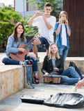 Smiling girls and boys with musical instruments. Smiling girls and boys teenagers friends with musical instruments together outdoors Royalty Free Stock Photo