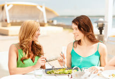 Smiling girls in cafe on the beach Royalty Free Stock Image