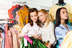 Smiling girls choose clothes during sale Royalty Free Stock Photography