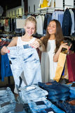 Smiling girls choosing denim trousers Stock Photography