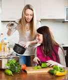 Smiling girls cooking in kitchen Royalty Free Stock Photography