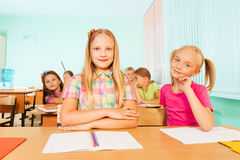 Smiling girls at desk looking straight Royalty Free Stock Image