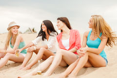 Smiling girls with drinks on the beach Royalty Free Stock Images
