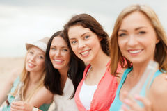 Smiling girls with drinks on the beach Stock Photography