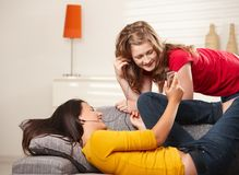 Smiling girls with earphones on couch Royalty Free Stock Images