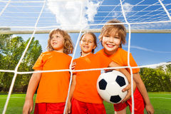 Smiling girls with football stand behind net. Three smiling girls in uniforms with football standing behind the white net of woodwork and smile happily Stock Photography