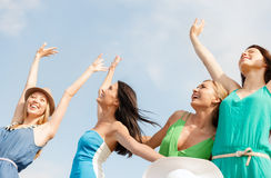 Smiling girls with hands up on the beach Royalty Free Stock Photo