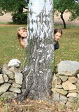 Smiling girls hiding behind tree Royalty Free Stock Images