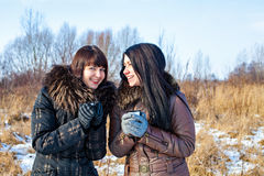 Smiling girls with hot drink at winter Royalty Free Stock Images